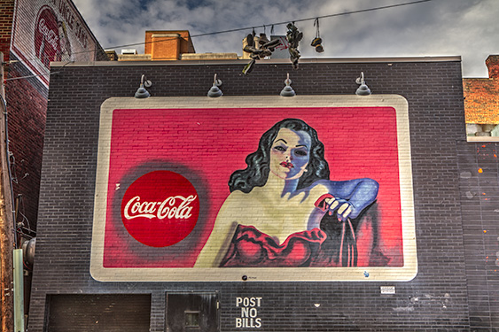 A billboard in the Oakland area of Pittsburgh displaying an old coca cola sing on the side of a building.