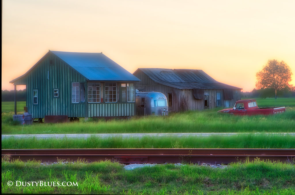 Dawn rises over an old shotgun shack and a rusty Ford truck and Airstream trailer.