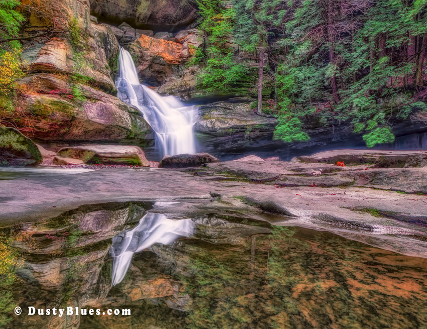 Cedar Falls with a reflection of the falls in the foreground from a pool of water.