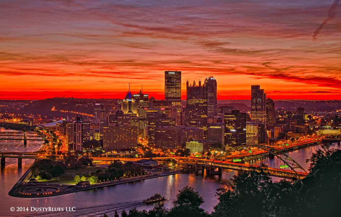 Blissful skies blush a reddish hue as a tug heads up river. Civil twilight as the city begins another bustling day. A red atmospheric...
