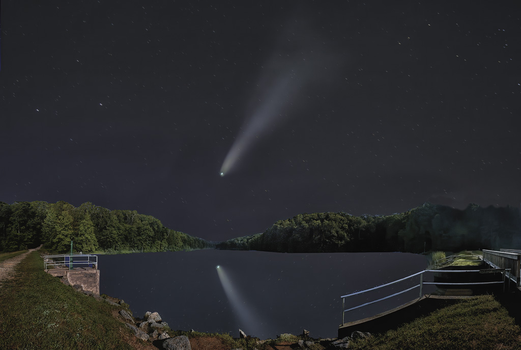 The Neowise comet races into the distant cosmos as it's reflection glows in the water.