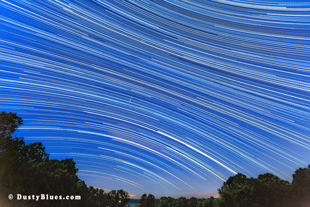 A full moon sky and the star trails of the Milky Way captured over seven hours of night in the Hocking Hills.